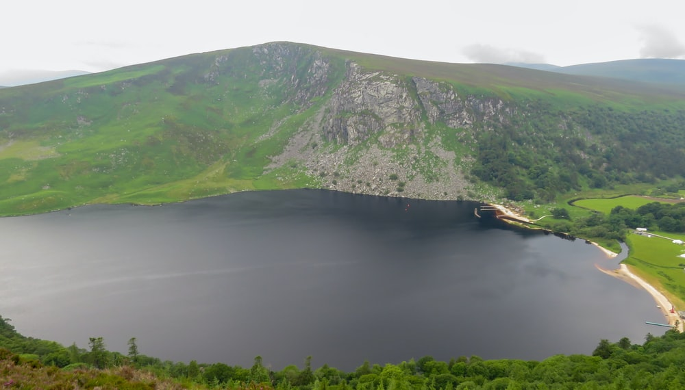 green and gray mountain beside body of water during daytime