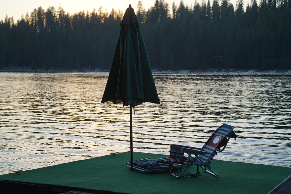 black and green camping chair near body of water during daytime