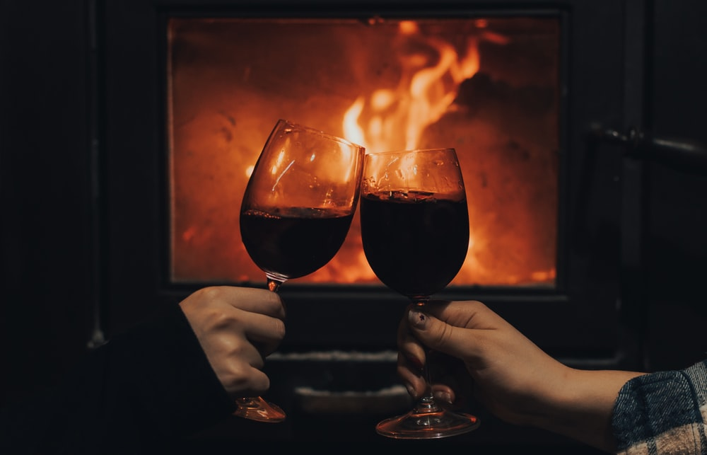 person holding wine glass with fire