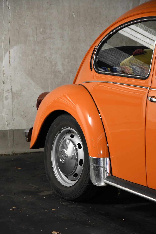 orange car parked beside white wall