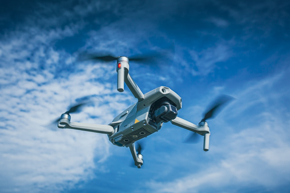 white and black drone flying under blue sky during daytime
