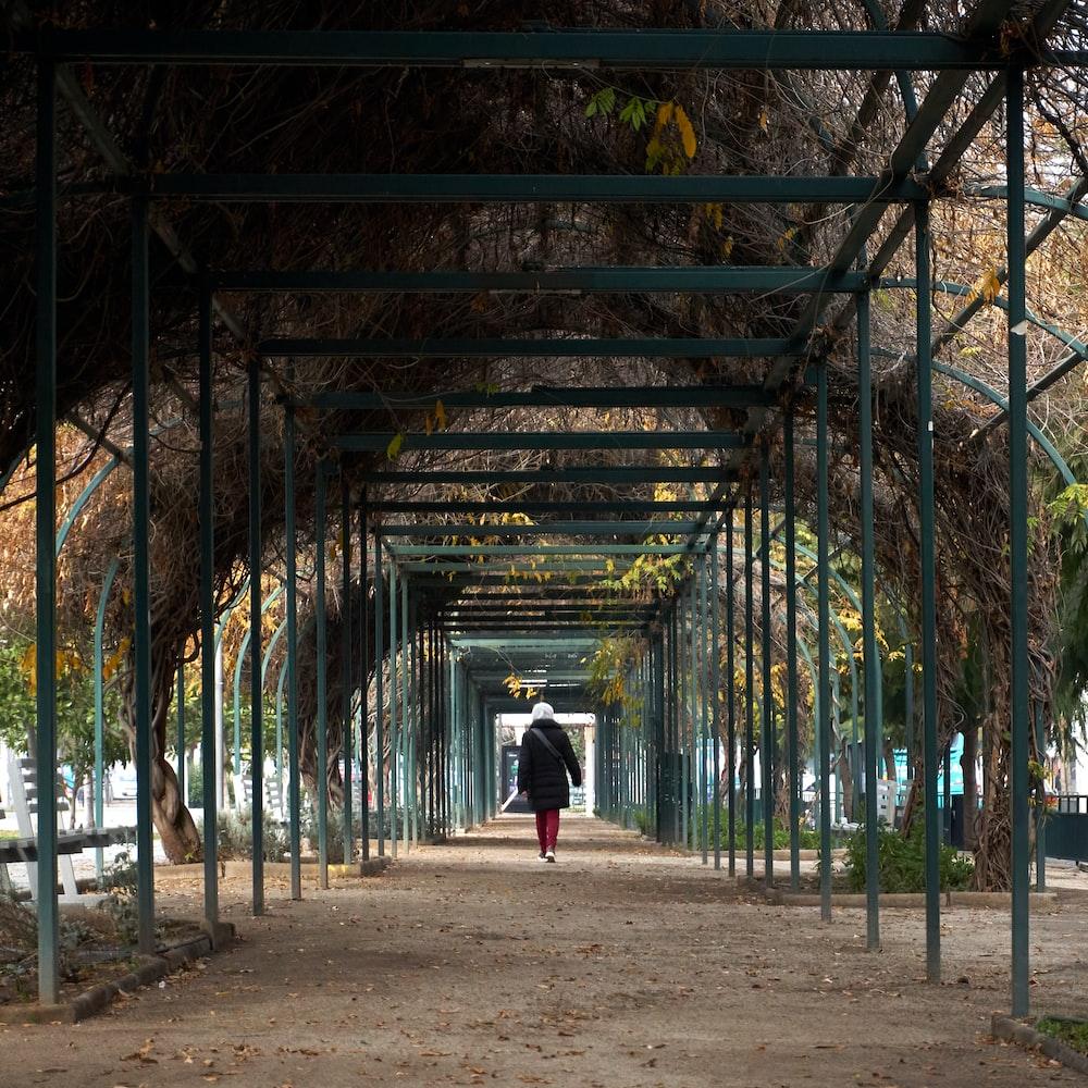 person in black jacket walking on pathway