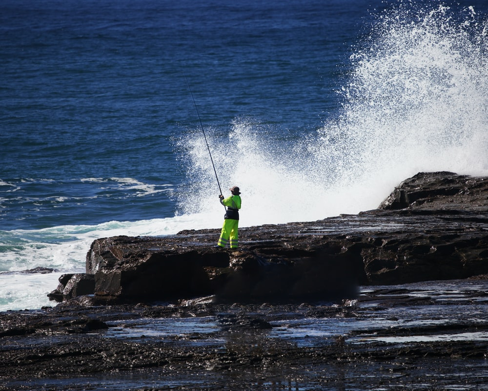 man in green shirt and green pants standing on rock near sea during daytime