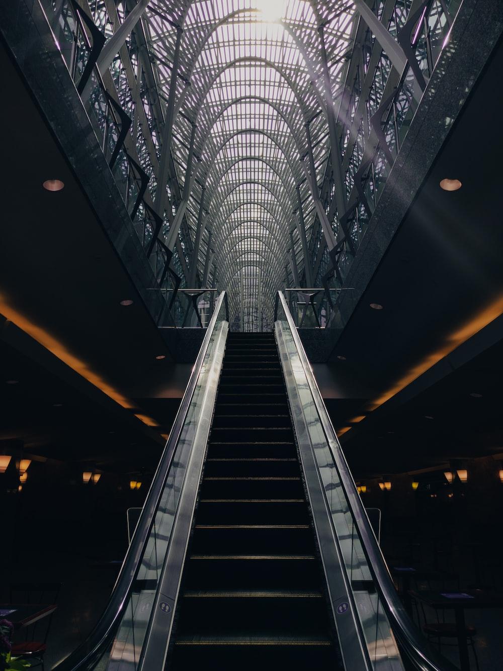 gray and black escalator in a tunnel