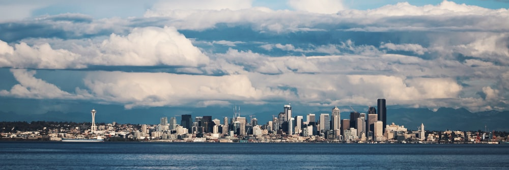 city skyline under white clouds and blue sky during daytime