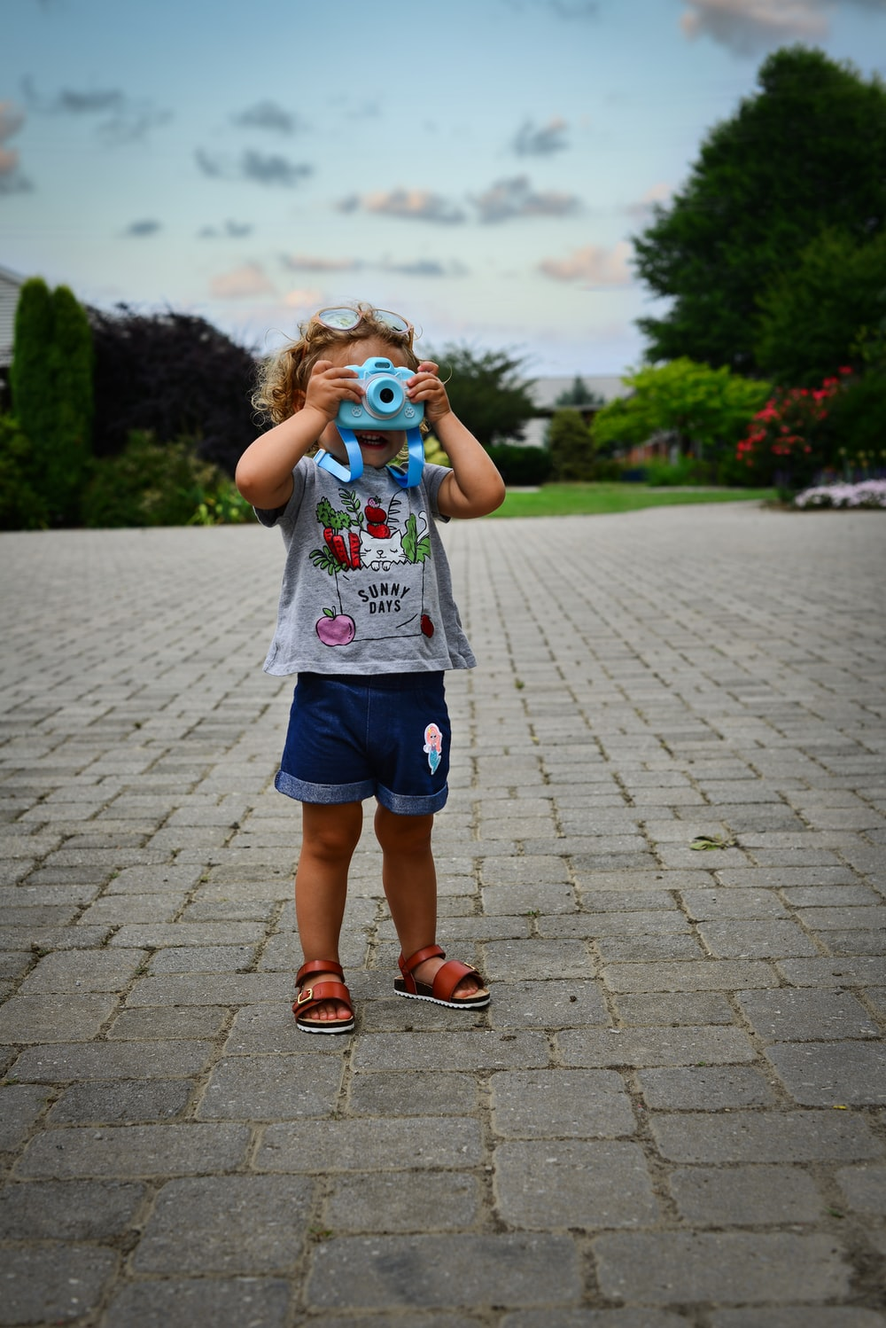 girl in white and pink floral shirt and blue denim shorts standing on gray concrete pathway