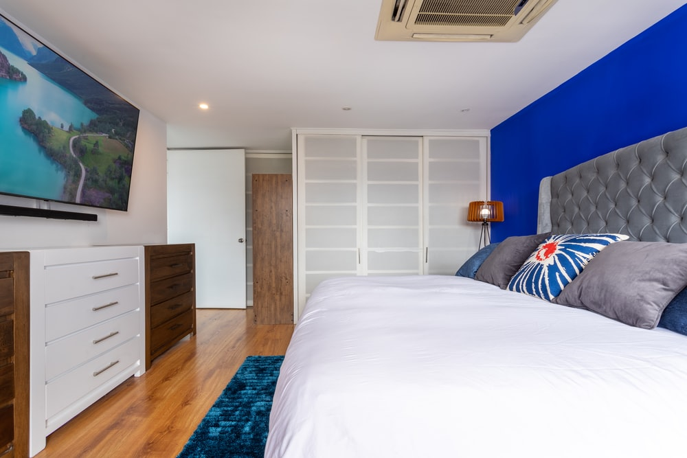white bed linen near brown wooden cabinet