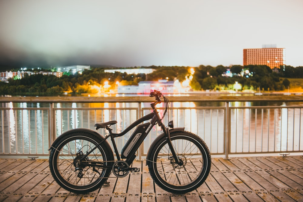 black and red bicycle on brown wooden dock during daytime