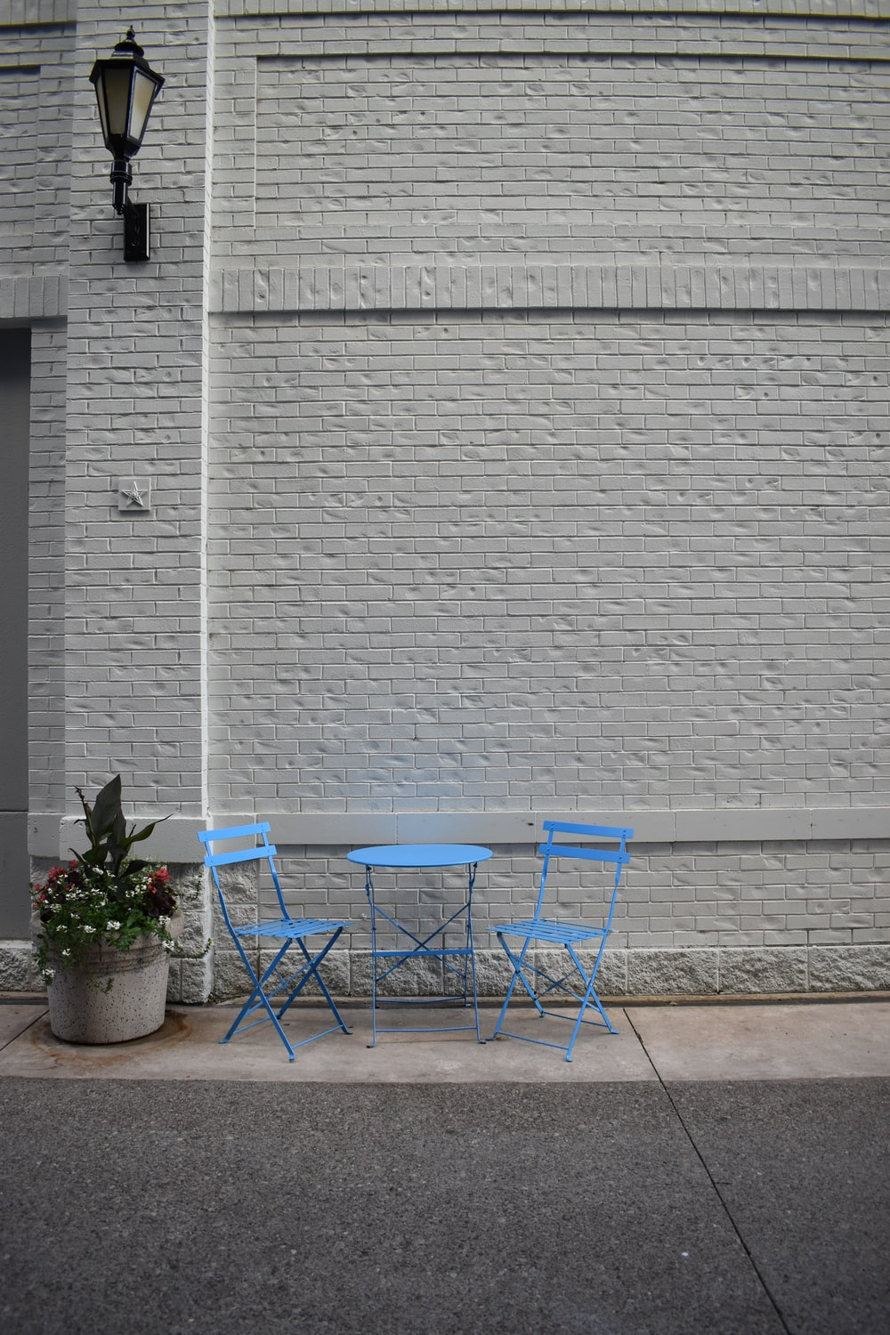 blue metal chairs beside gray wall