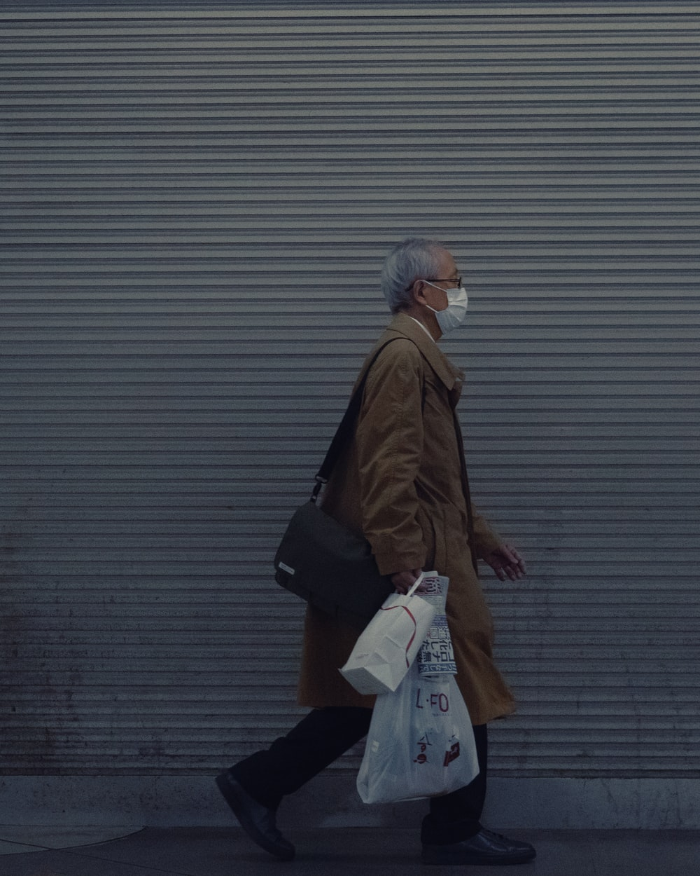 woman in brown coat holding white plastic bag