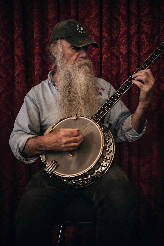 man in grey shirt playing acoustic guitar