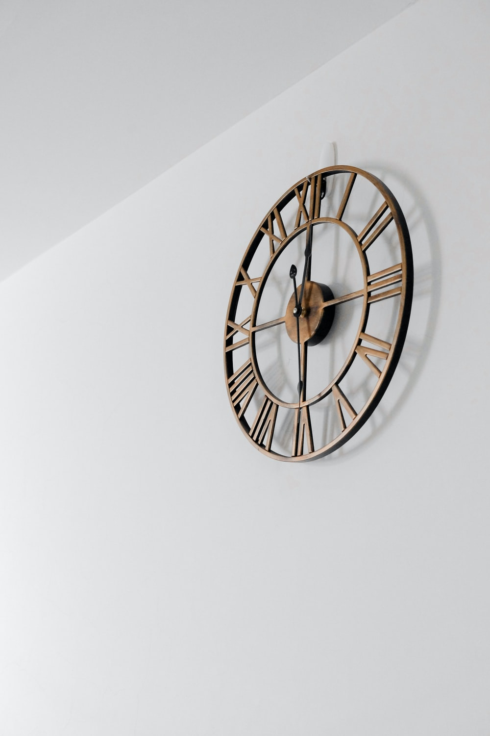 gold round wall clock on white painted wall