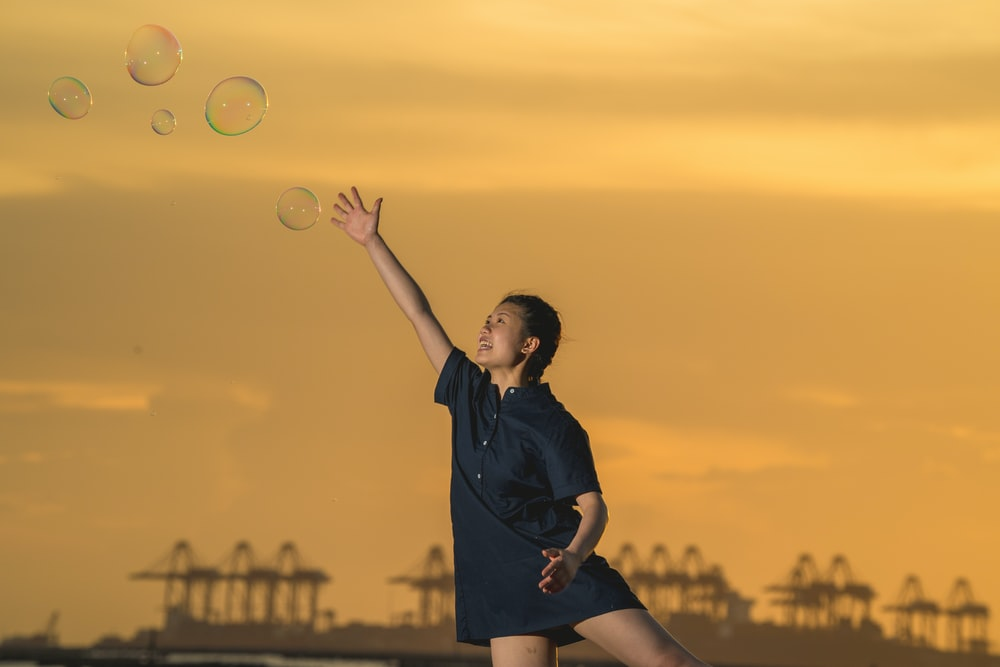 woman in black dress holding bubbles during sunset