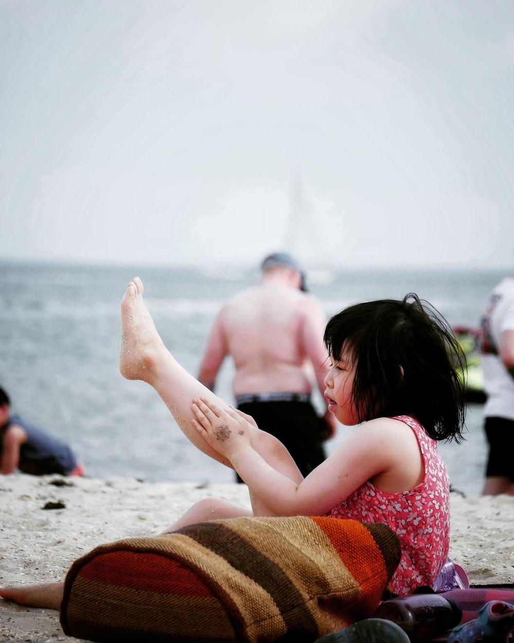 2 women sitting on beach shore during daytime