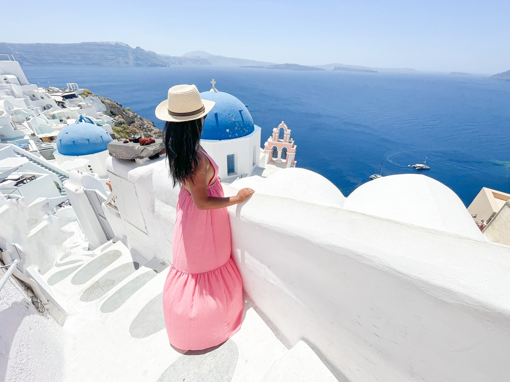 woman in pink dress and white hat standing on white concrete surface during daytime