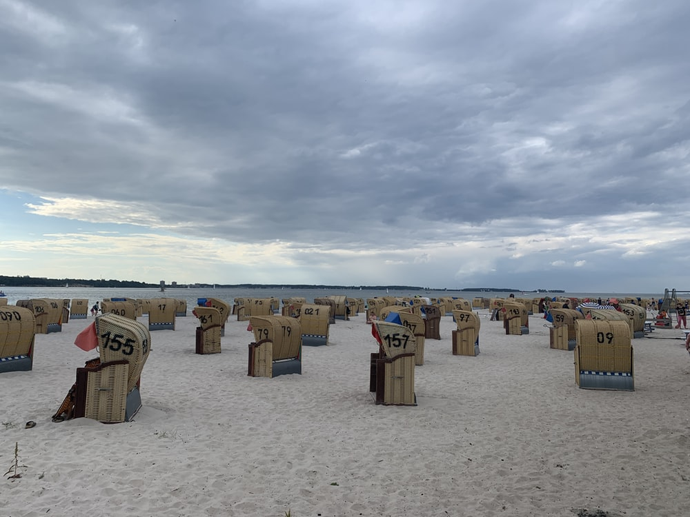 brown wooden houses on white sand under white clouds during daytime
