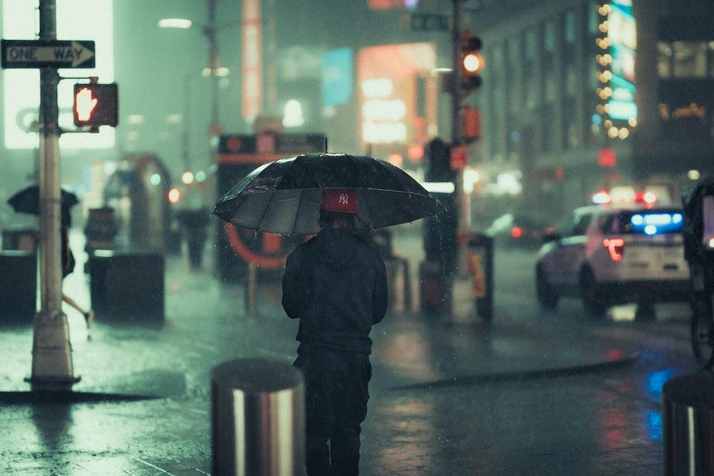 man in black jacket holding umbrella walking on street during night time