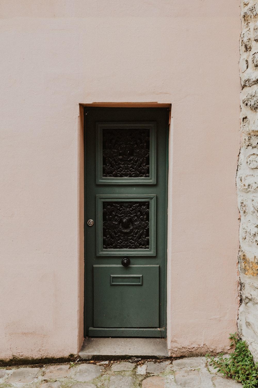 black wooden door on white concrete wall