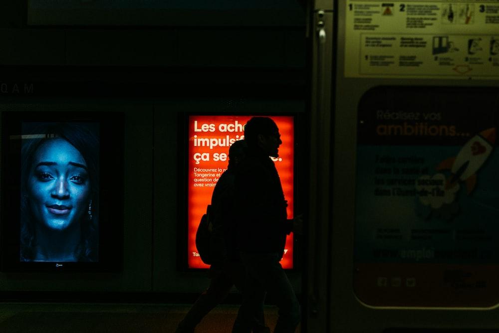 man in red jacket standing near window