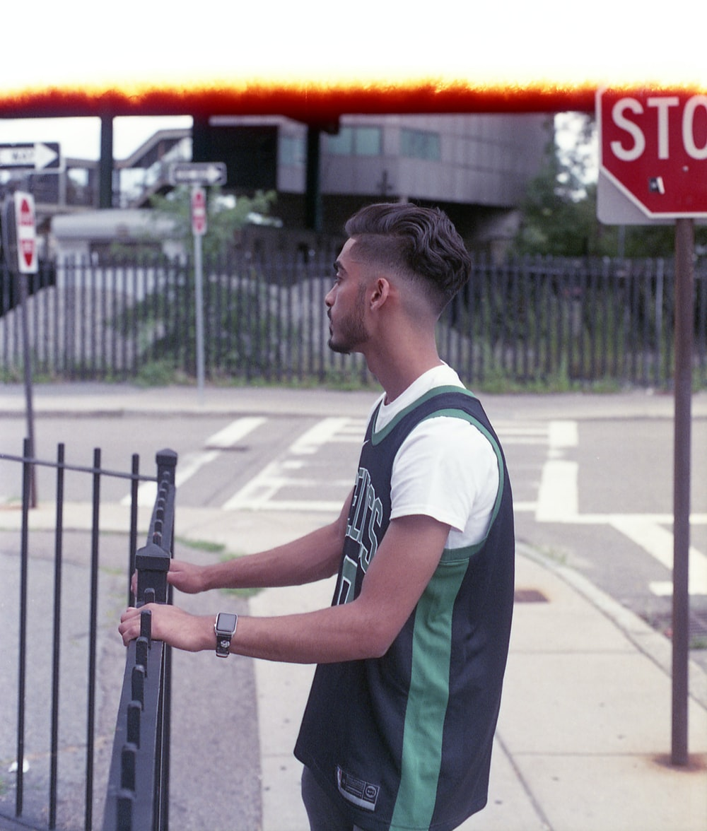 man in green and white polo shirt standing near black metal fence during daytime