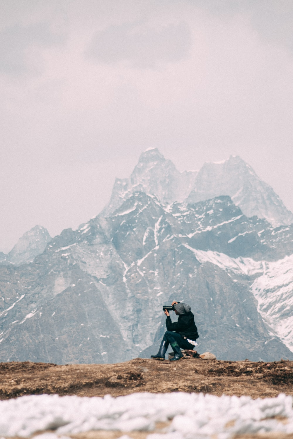 person in black jacket and black pants sitting on rock mountain during daytime
