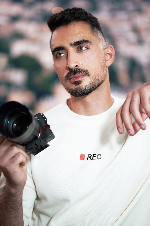 man in white crew neck t-shirt holding black dslr camera