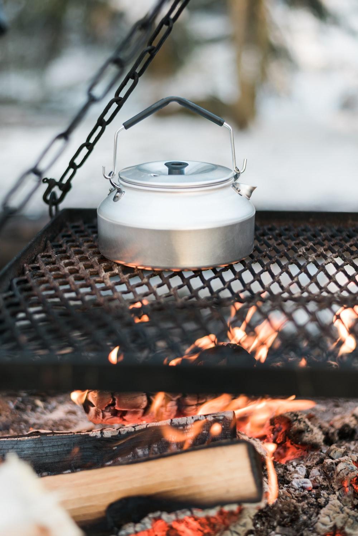 white ceramic pot on black metal grill