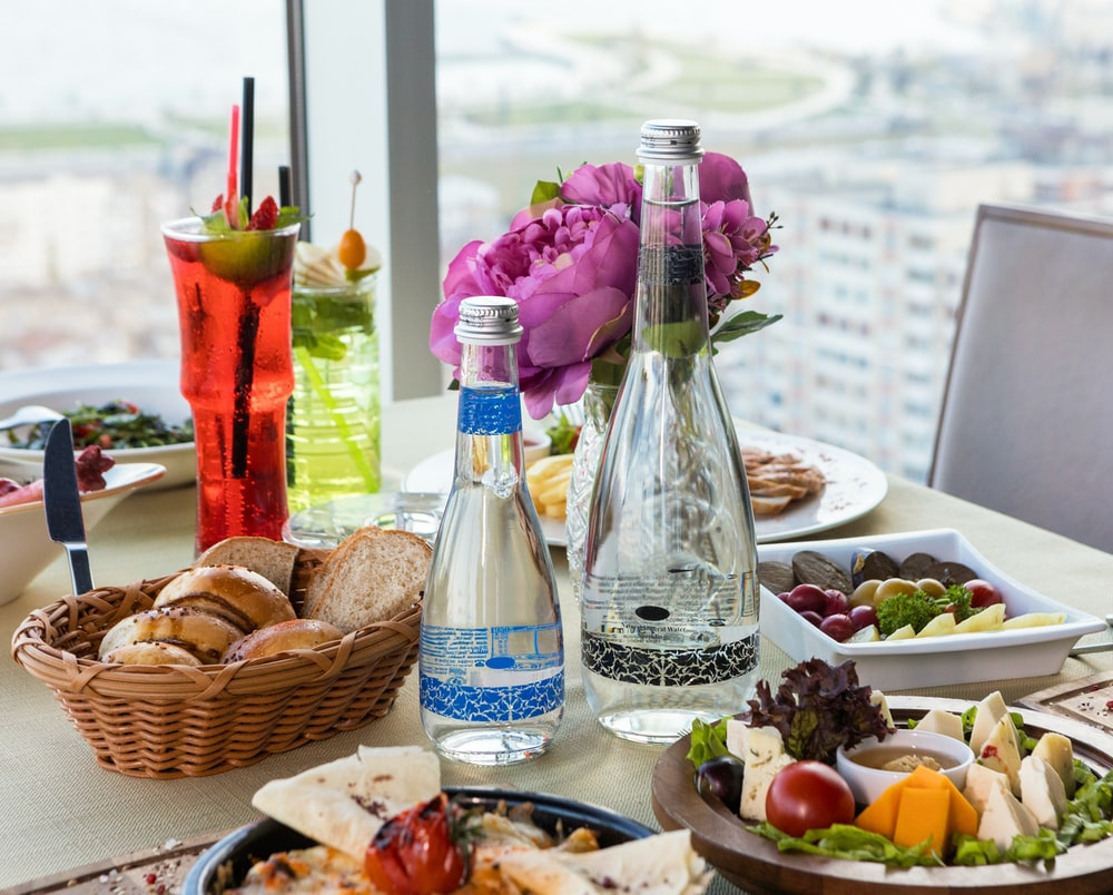 clear glass bottle beside brown woven basket with fruits on table