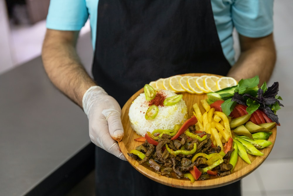 person holding brown round plate with burger
