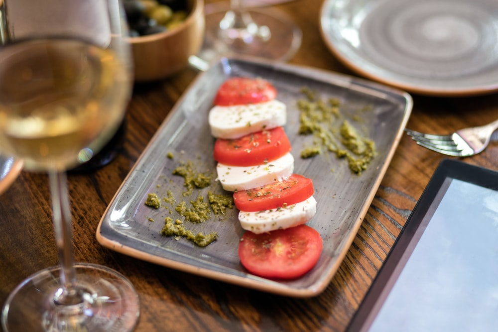 sliced tomato and green vegetable on stainless steel tray