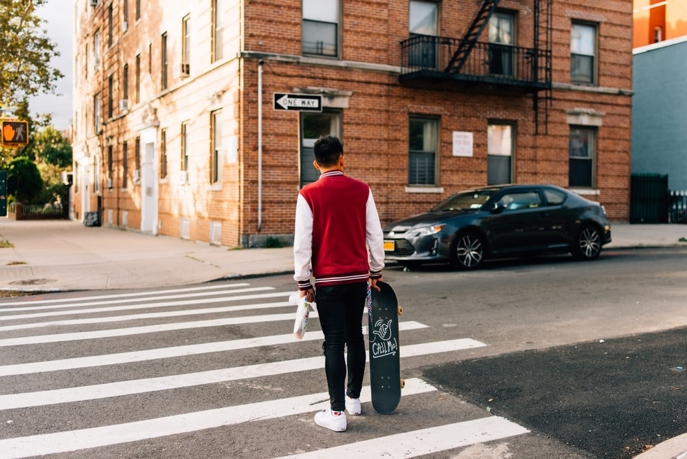 man in red and white long sleeve shirt and black pants walking on pedestrian lane during