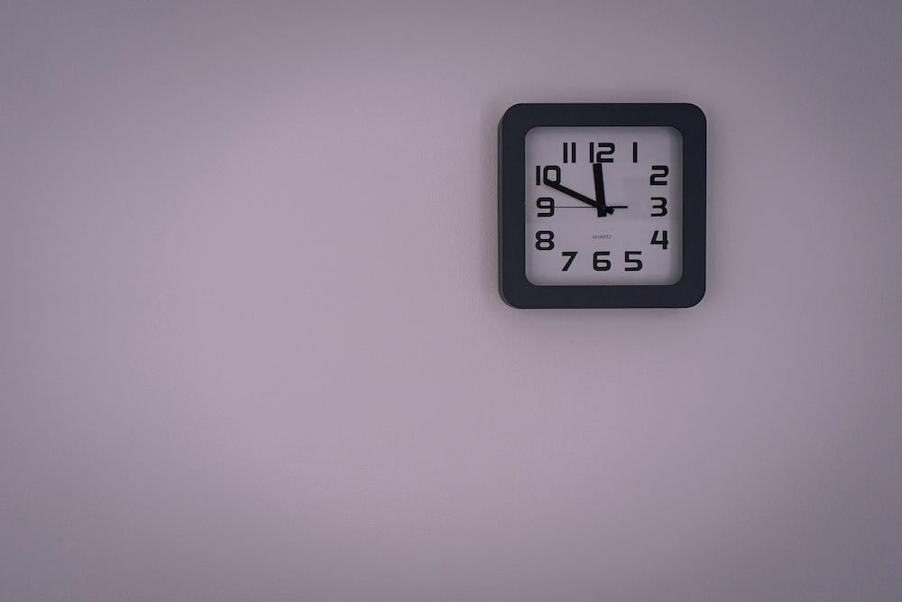 black and white analog wall clock at 11 00