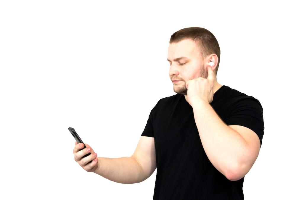 man in black crew neck t-shirt holding black pen