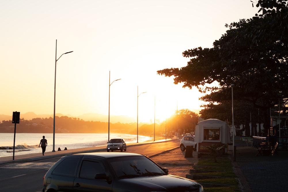 black sedan on road during sunset