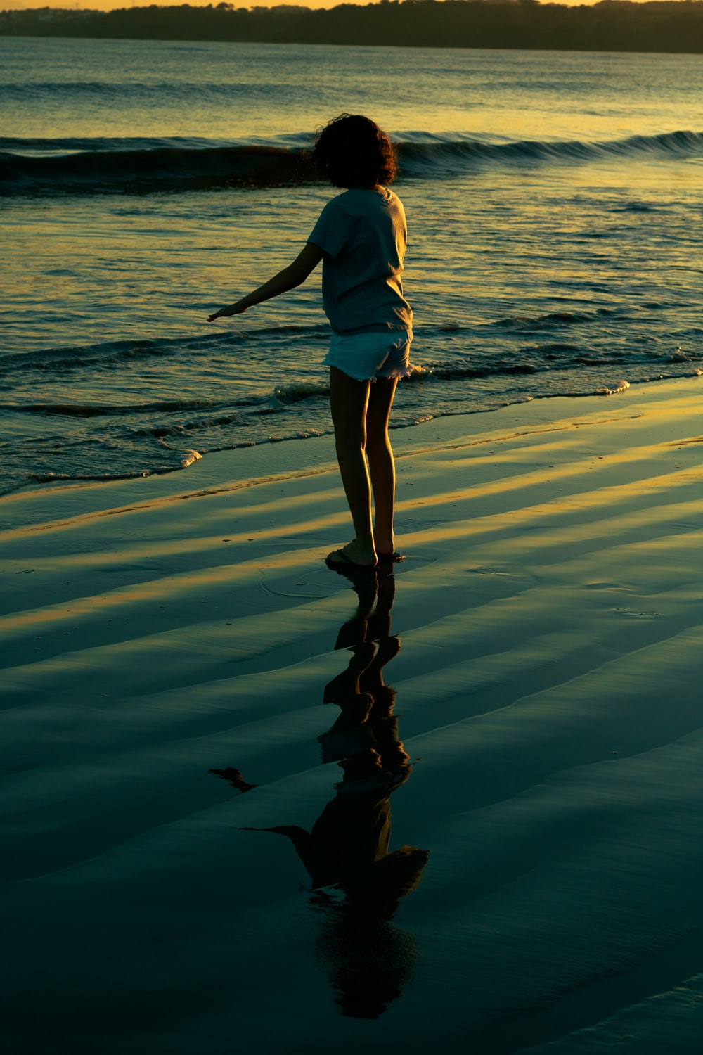 woman in white shirt and white shorts standing on seashore during daytime