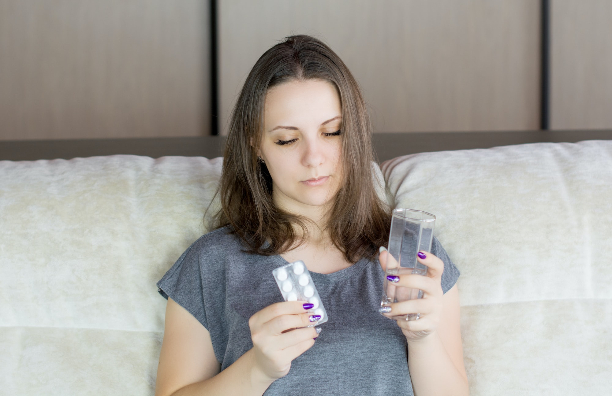 Woman suffers headache, takes pill while sitting in sofa with glass of water.