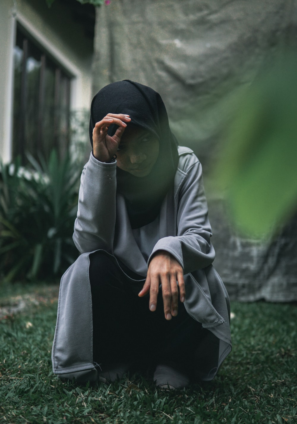 man in white thobe and black hijab sitting on green grass during daytime