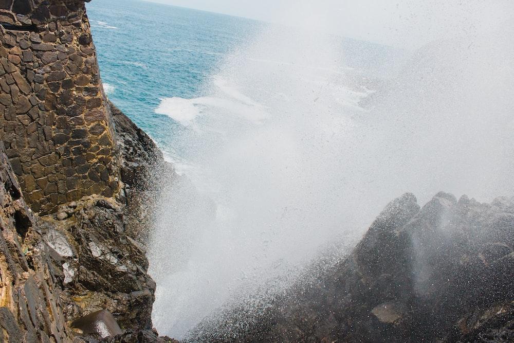 ocean waves hitting brown rocky shore during daytime