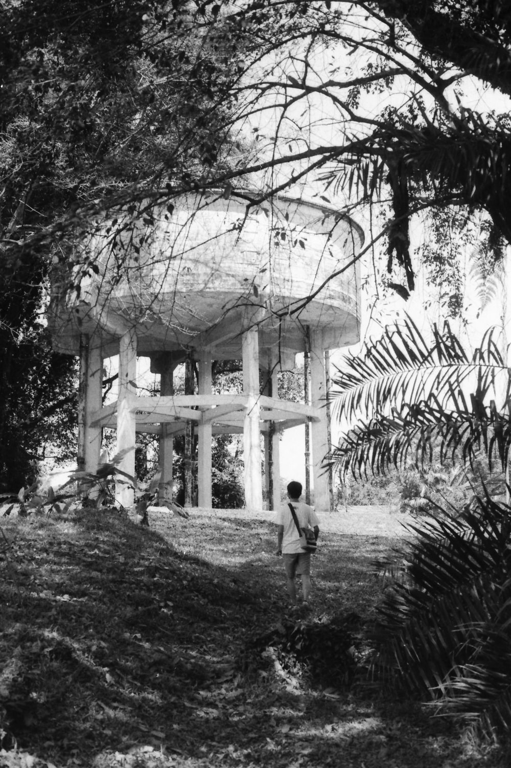grayscale photo of man in black jacket and pants standing near building
