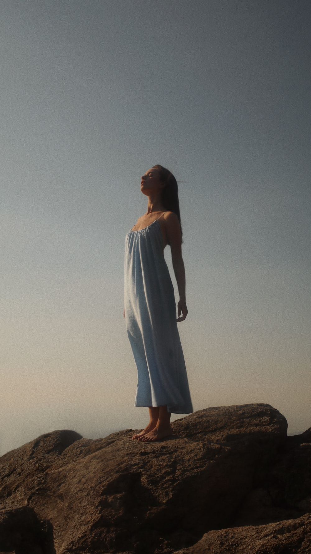 woman in white dress standing on brown rock during daytime
