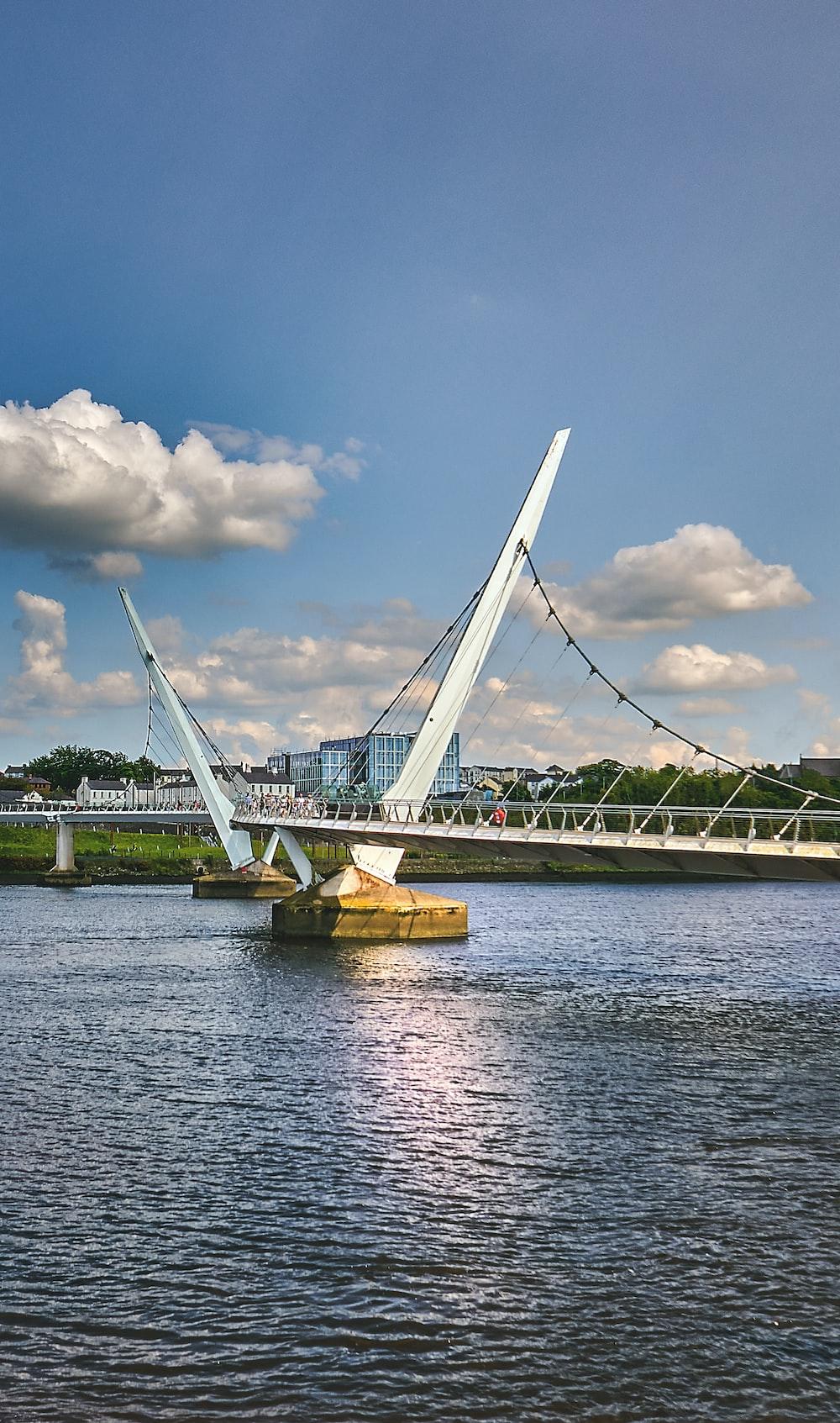 white bridge over body of water under blue sky during daytime
