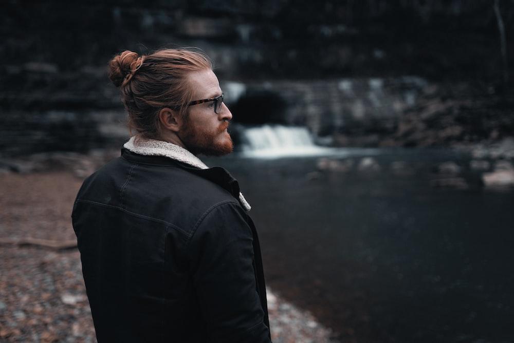 man in black jacket standing near river during daytime