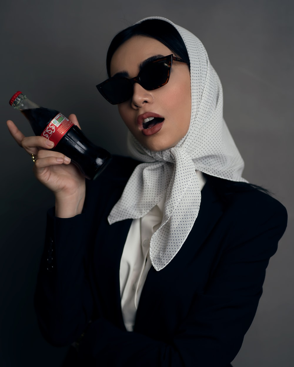 woman in black long sleeve shirt holding black bottle