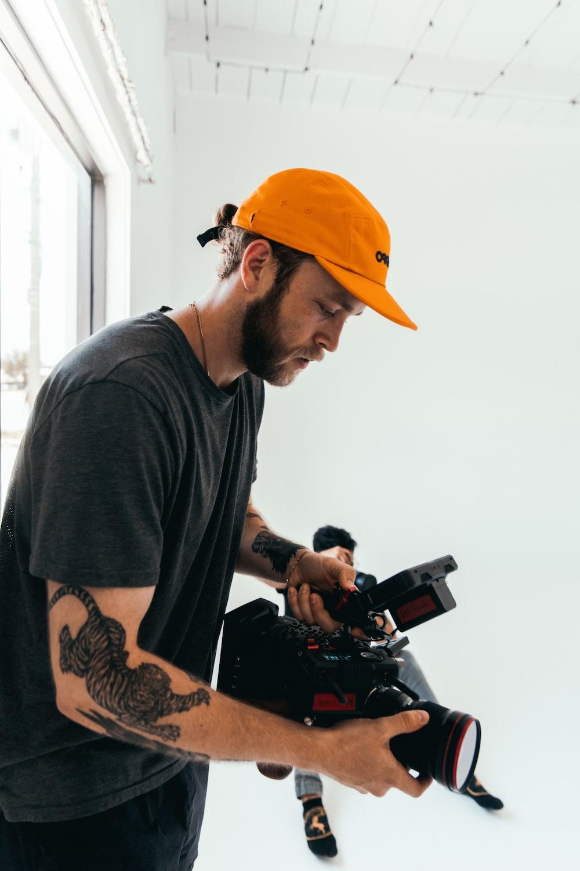 man in gray crew neck t-shirt wearing orange cap holding black dslr camera