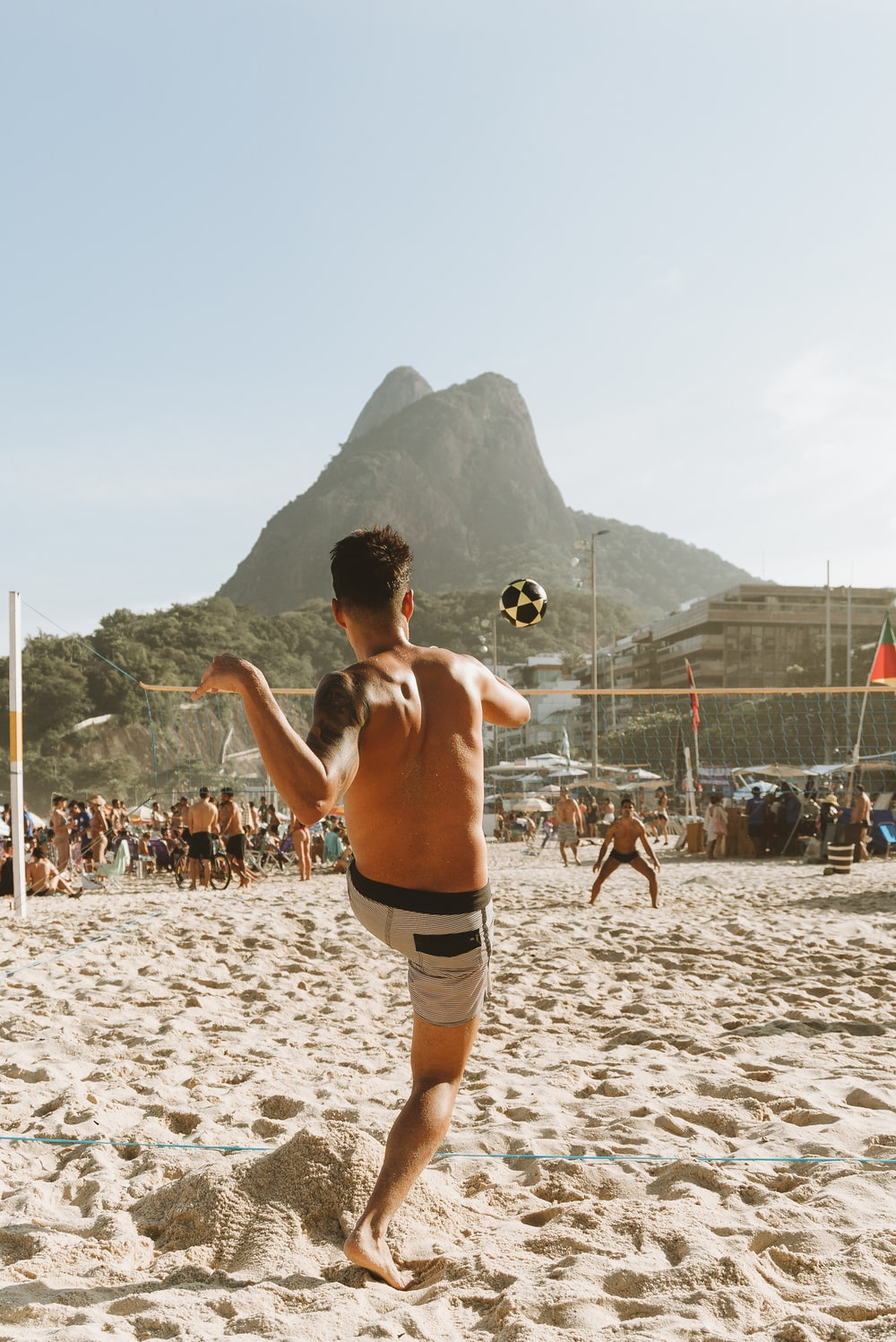 topless man in black shorts running on white sand during daytime
