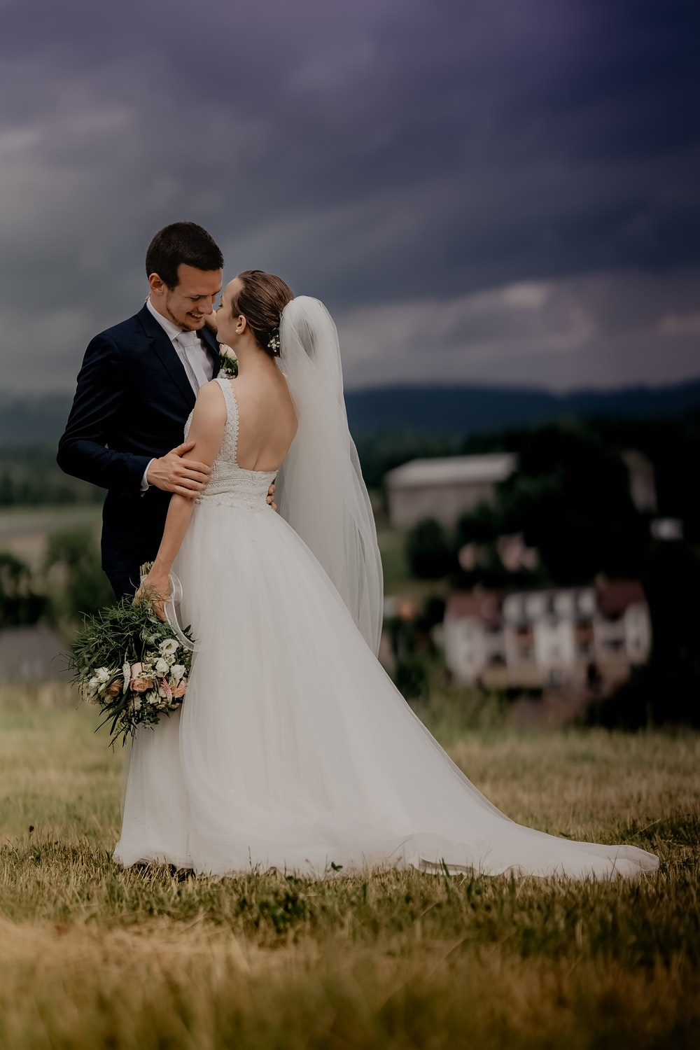 man in black suit kissing woman in white wedding dress on green grass field during daytime