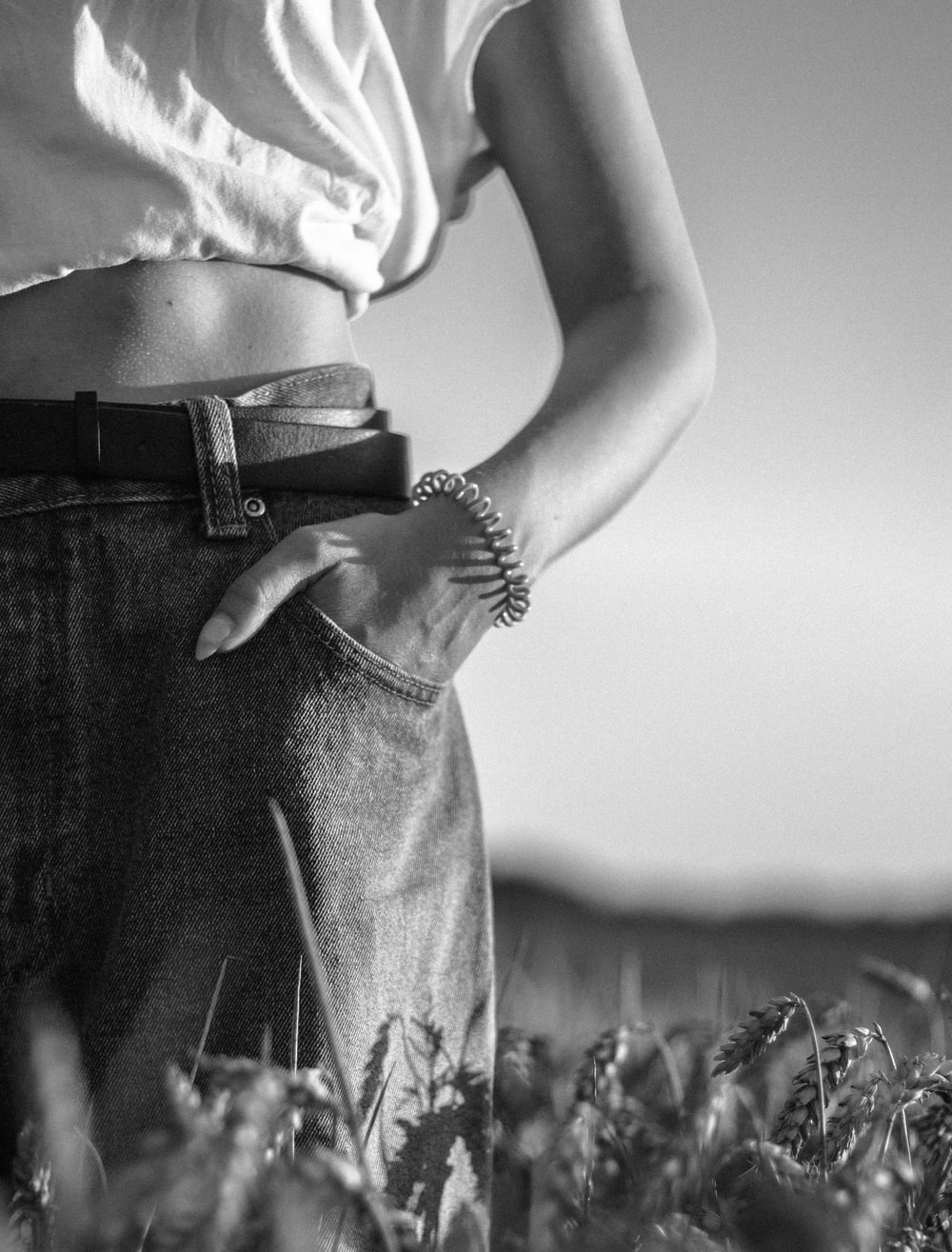 grayscale photo of woman in crop top and denim jeans