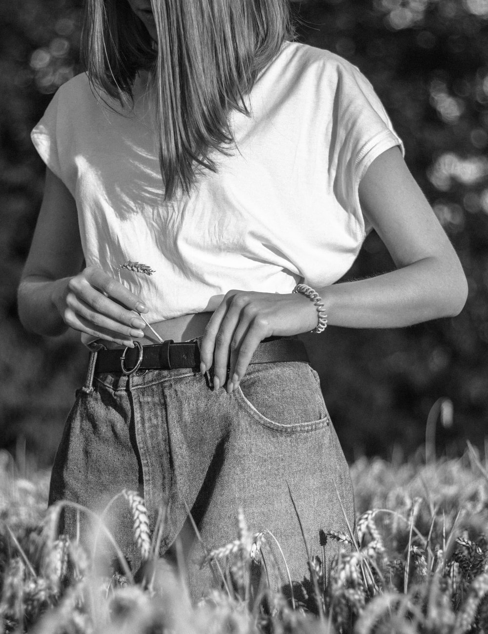 woman in white t-shirt and blue denim daisy dukes standing on grass field
