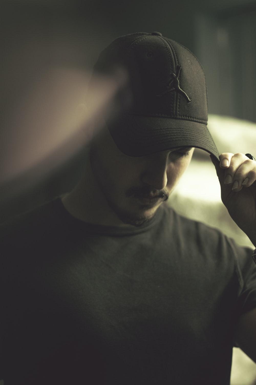 man in black crew neck shirt wearing black hat