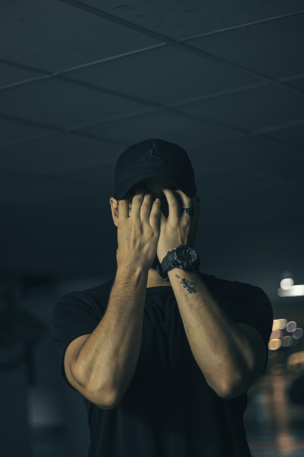 man in black crew neck t-shirt covering face with hands